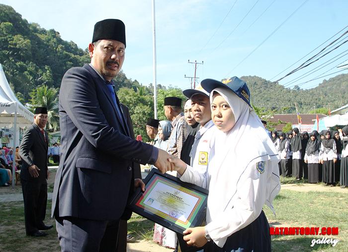 Sekretaris Daerah Kabupaten Kepulauan Anambas, Sahtiar saat menyerahkan penghargaan kepada perwakilan pelajar yang berprestasi