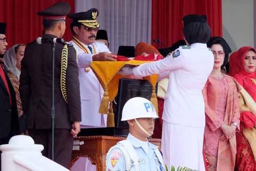 Gubernur menyerahkan bendera Merah Putih kepada pembawa baki untuk dikibarkan.