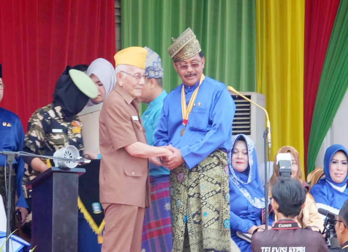 Salah seorang pejuang Provinsi Kepri memberikan tanda kehormatan kepada Gubernur Nurdin Basirun