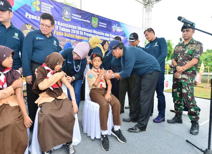 Nurdin saat mengimunisasi MR salah seorang anak SD di Batam