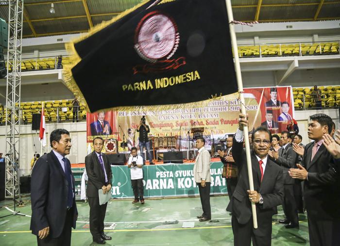 Jumaga Nadeak, S.H saat mengangkat bendera Parna Indonesia usai pelantikan